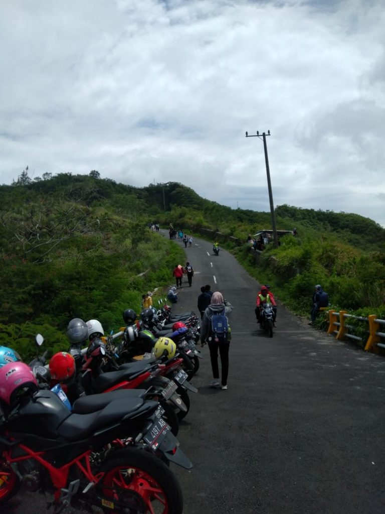 A group of people on a motorcycle parked on the side of a road  Description automatically generated